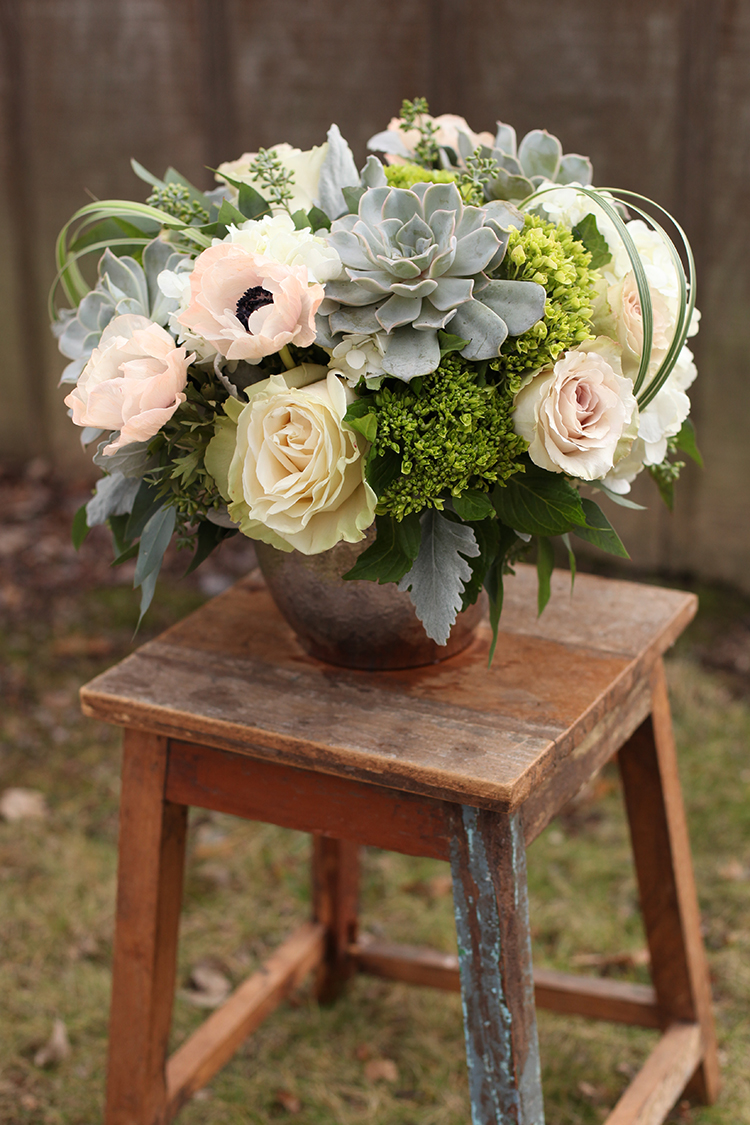Modern centerpiece by Cincinnati wedding florist Floral Verde LLC, with succulents, peach anemones, Quicksand roses, Mondial roses, green hydrangea, dusty miller, seeded eucalyptus and variegated lily grass.