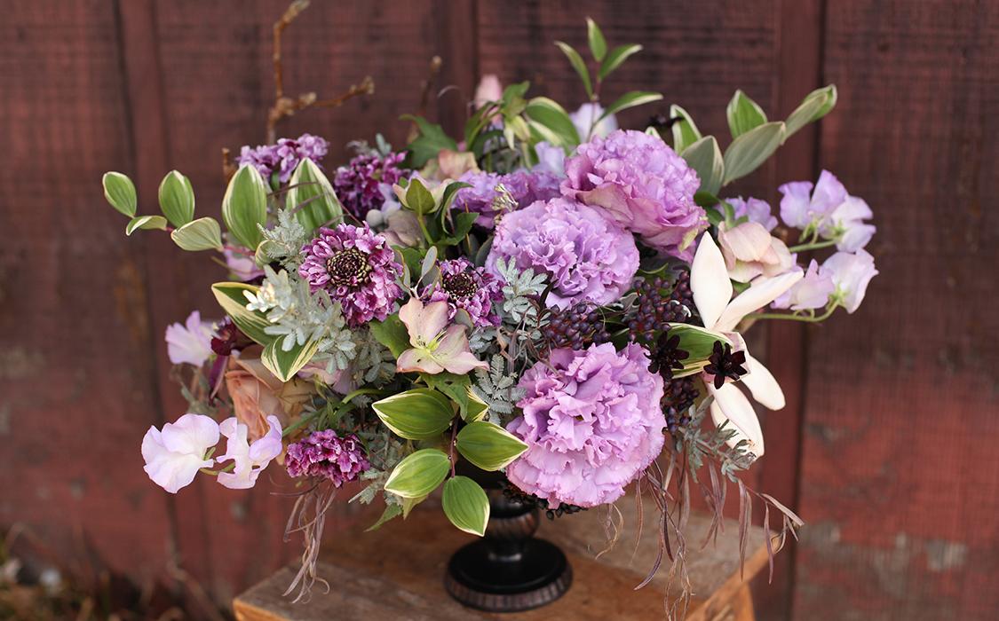 Centerpiece by Cincinnati wedding florist Floral Verde LLC, with Chocolate cosmos, viburnum tinus, agonis,purple scabiosa, lavender lisianthus, Amnesia roses, feather acacia, helleborus, magnolia and polygonatum.