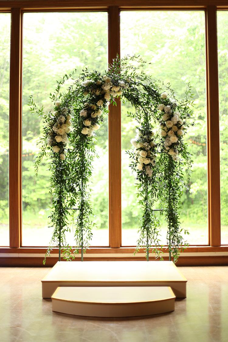 Wedding arch at YMCA Camp Kern Schiewetz Assembly Hall. Flowers by Cincinnati wedding florist Floral Verde.