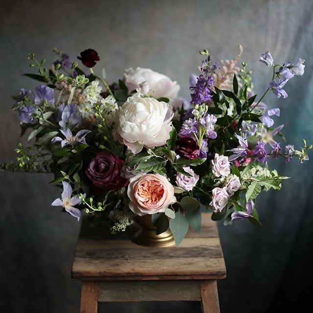 A centerpiece from Bailey and David's wedding with purple larkspur from @thatgirlsflowers.
