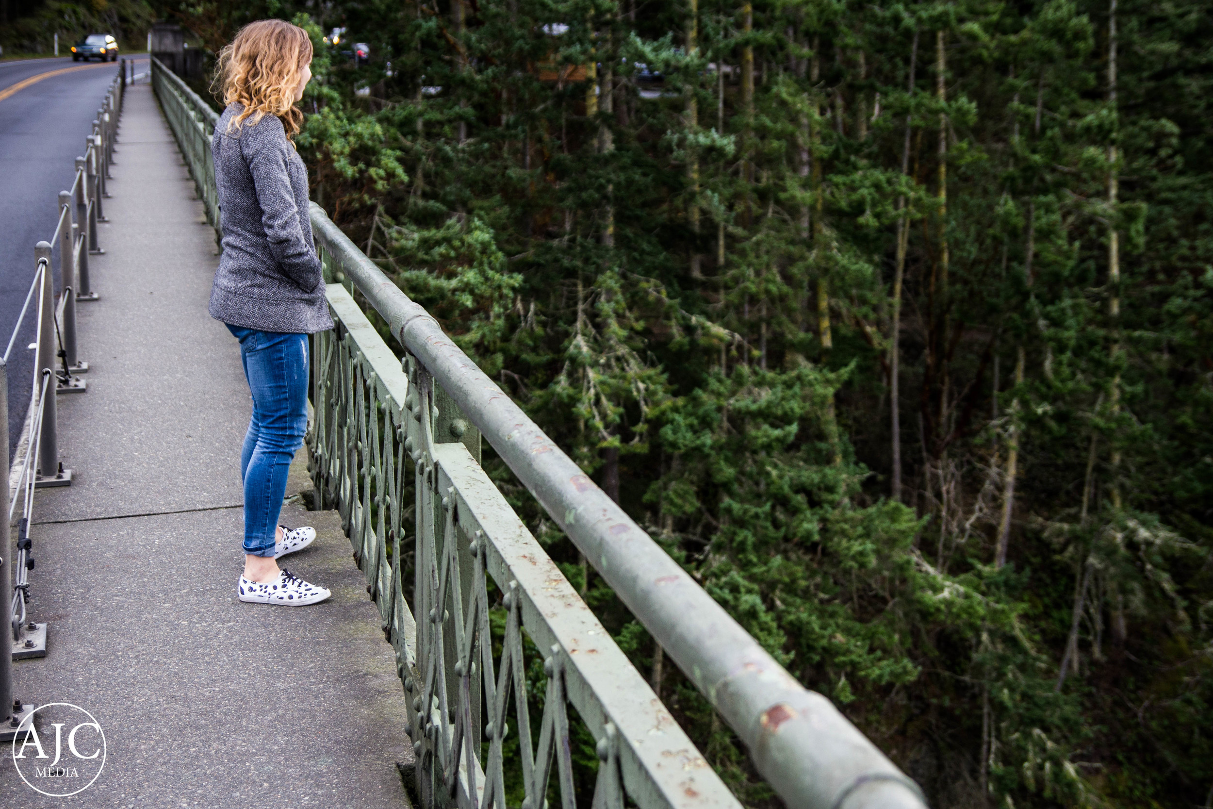 Alison peers over the edge at the water of Deception Pass.