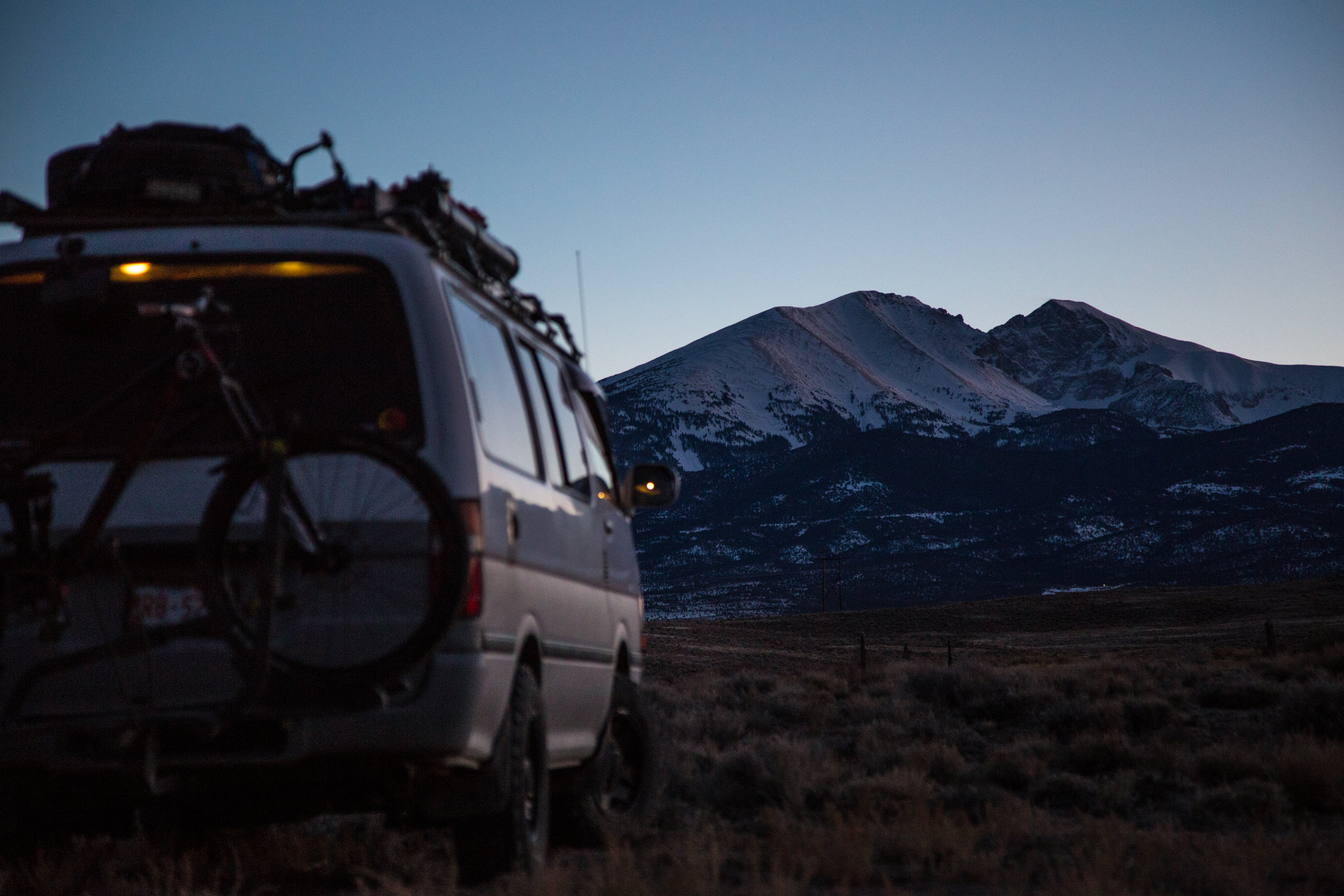 Watching the sunset on a snow capped mountain while being parked in a desert.