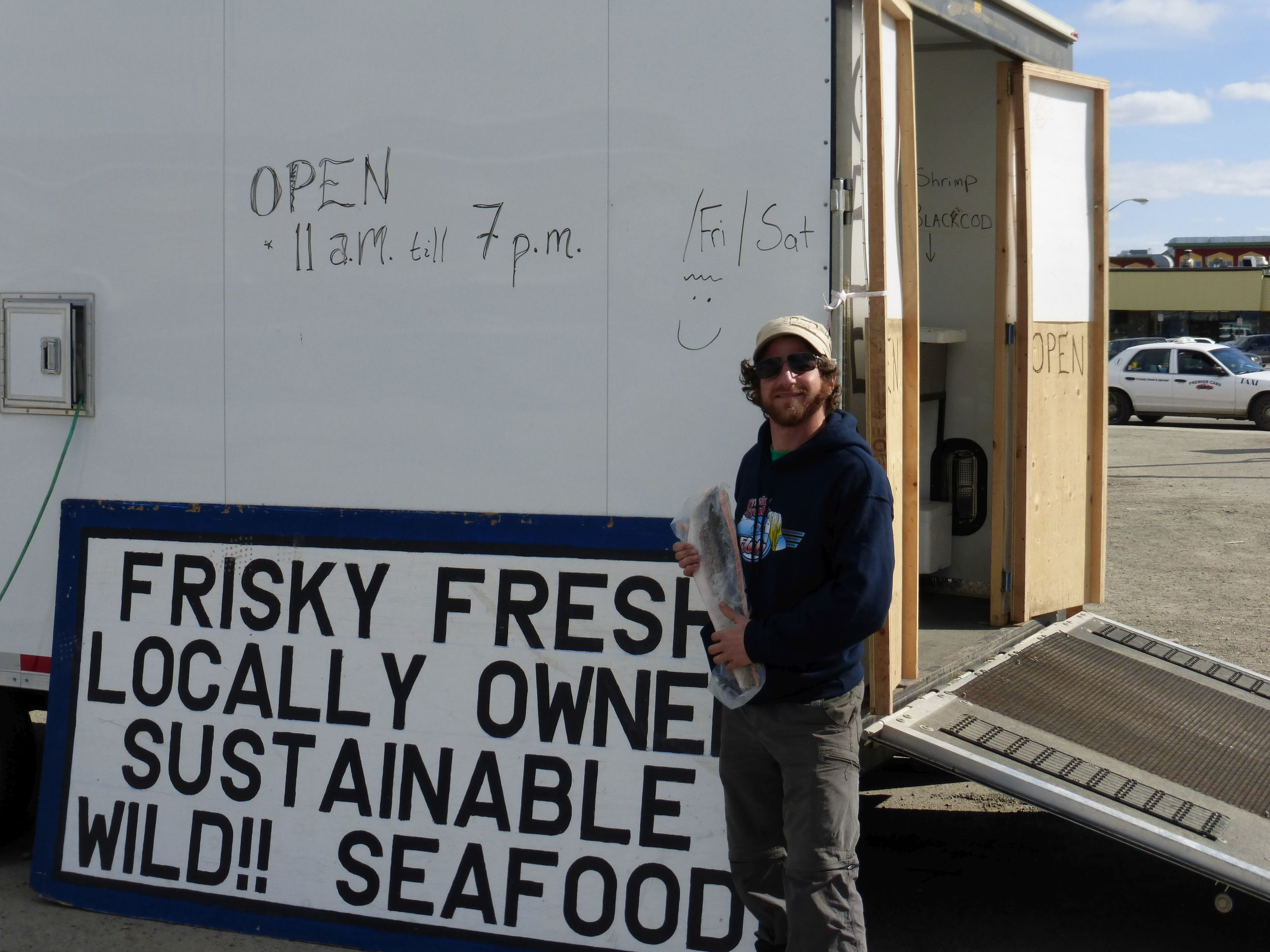 His name is Monkey.  He delivers seafood from Alaska and sells it here.  When not busy with customers he agrees to pose with a fish for people on bikes.