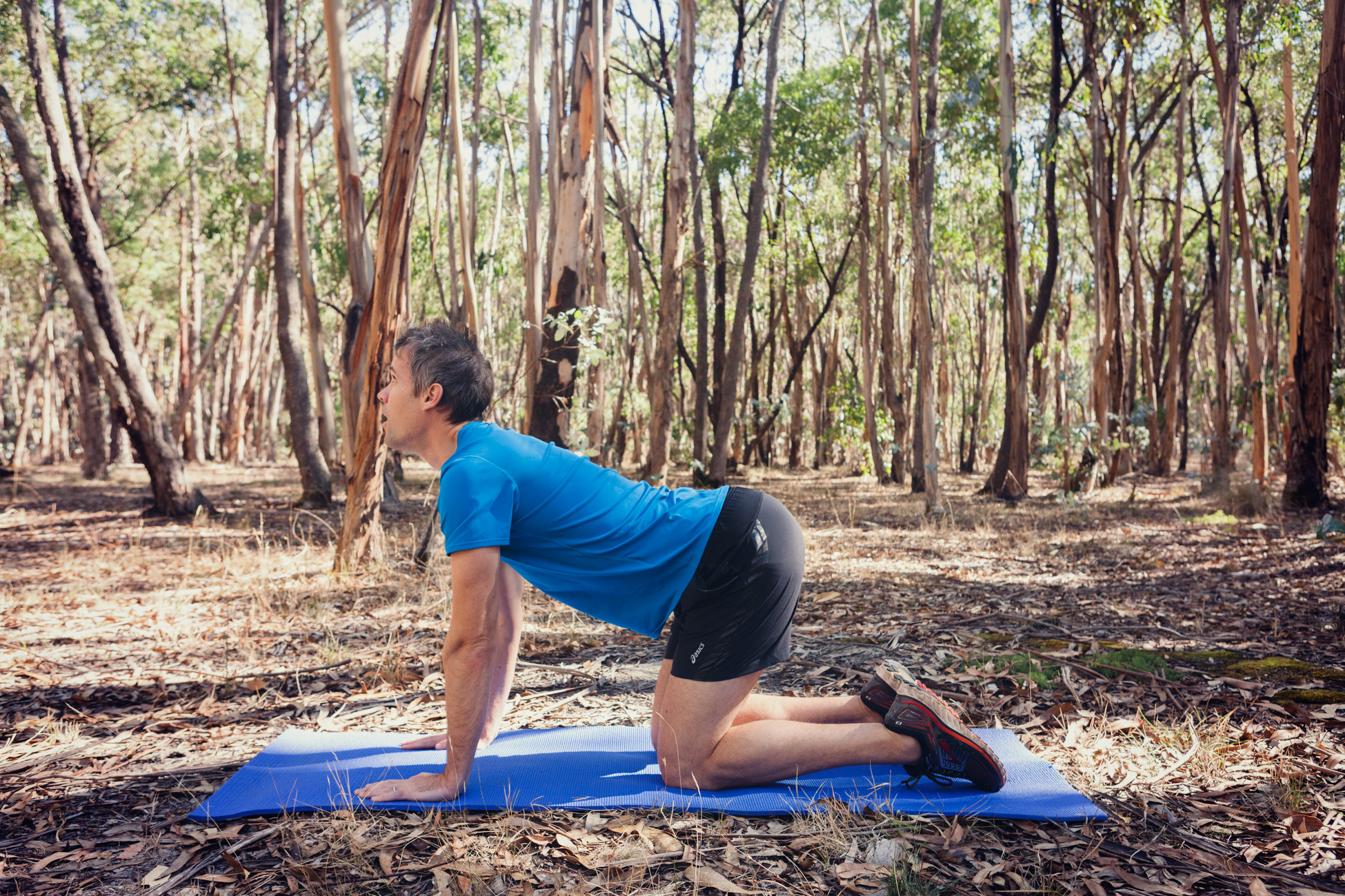 Start on your hands and knees with your back in a neutral position. Arch your back, lifting your head up and pushing your tail bone out, making a dish with your spine. Hold this position for one breath.