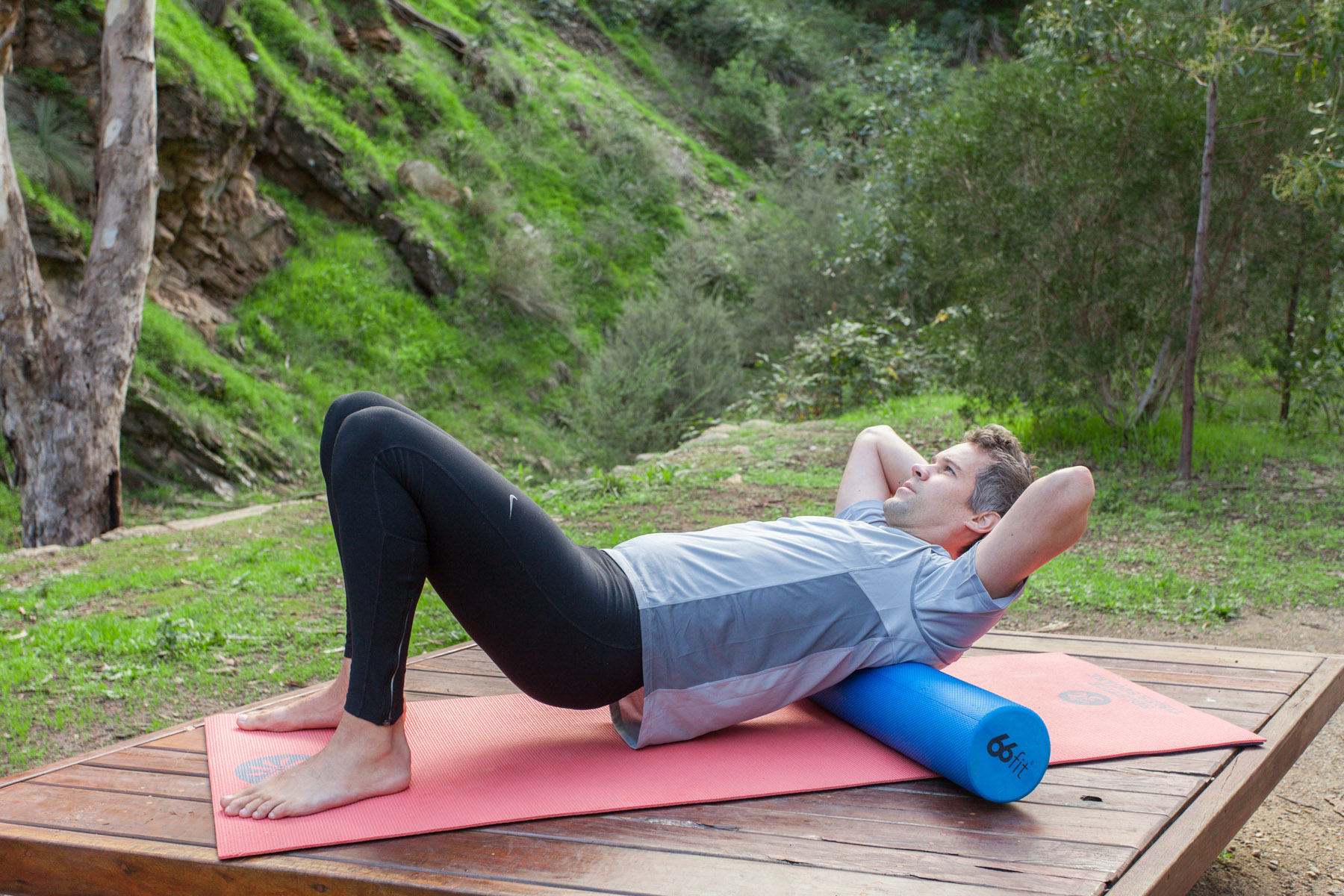 Lie with a foam roller in your mid-back, and hug your arms across your chest to open up the upper back. Lift your hips off the mat, and roll back and forth for about 30 seconds, pushing with your legs. You may feel a few cracks and pops which is a great sign your are releasing the joint stiffness.