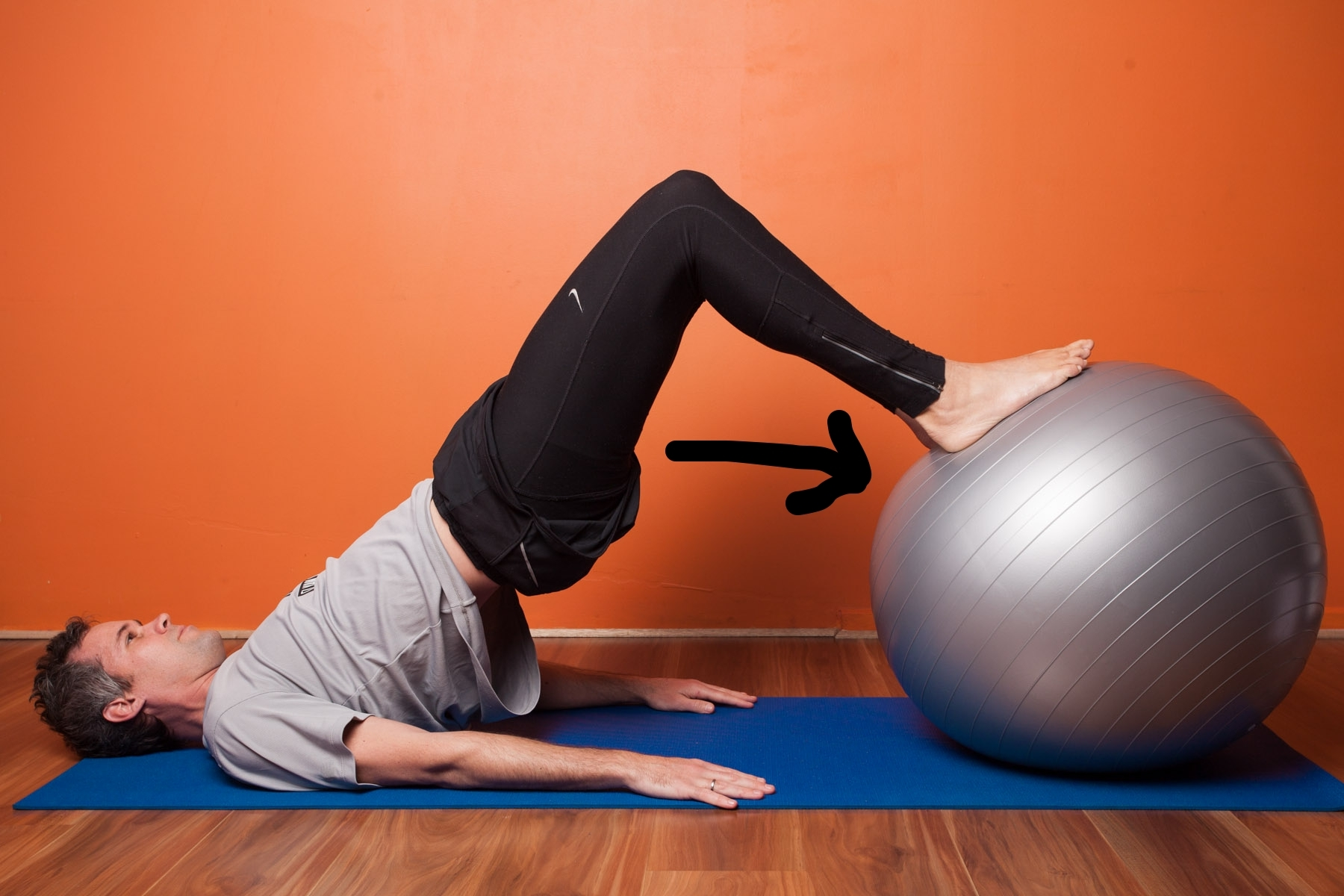 The perfect Eccentric Hamstring Exercise: Strengthening  AND  lengthening.    Quickly pull the ball in towards you and then SLOWLY (slow as you can) lower the ball away from you.      Count to as least 5 seconds as you do this.      Repeat until fatigue. and then do another x 2 rounds.      If you can do x 30 reps pretty easily, try one legged.     Practicing this movement will have a direct improvement on your hamstring problems, especially for runners.