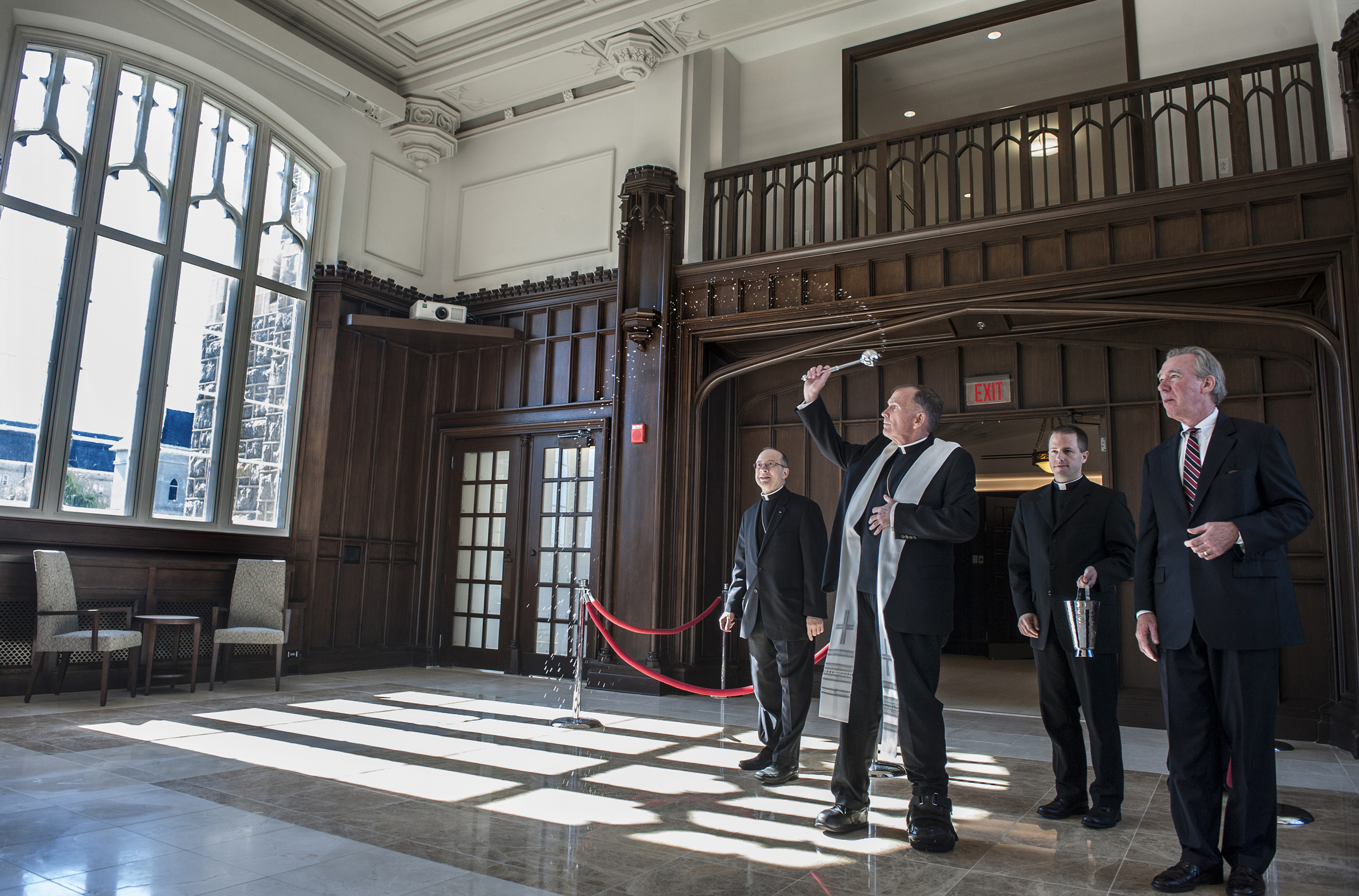 """Bishop David M O'Connell of Trenton blesses Heritage Hall during a dedication ceremony of the newly restored Father O'Connell Hall named in his honor. The former president of The Catholic University of America remarked """"My friends, thank you for doing this while I am alive."""""""