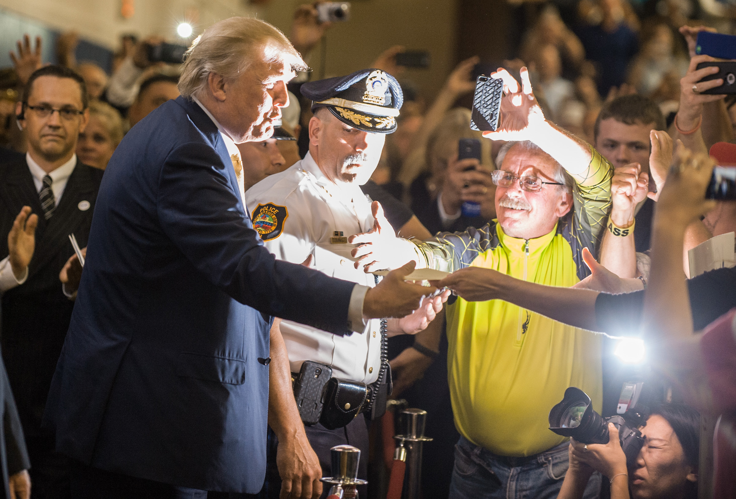 Donald Trump greets a frenzy of spectators jostling for photos as he enters the stage for a town Hall meeting in Rochester, New Hampshire. Trump was mobbed by fans on every step he took at the event.