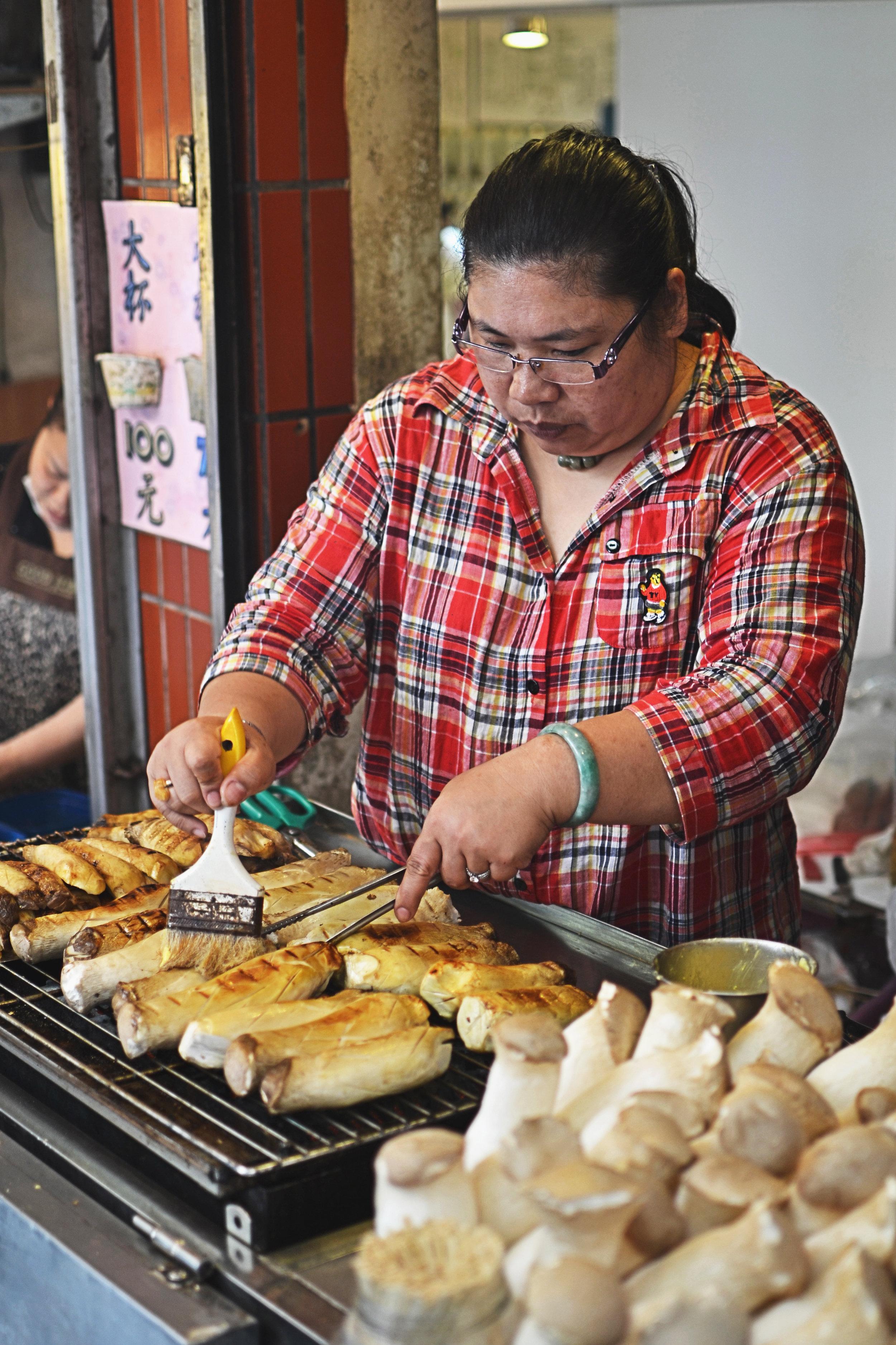 A woman grilling mushrooms at Jiufen, Taiwan
