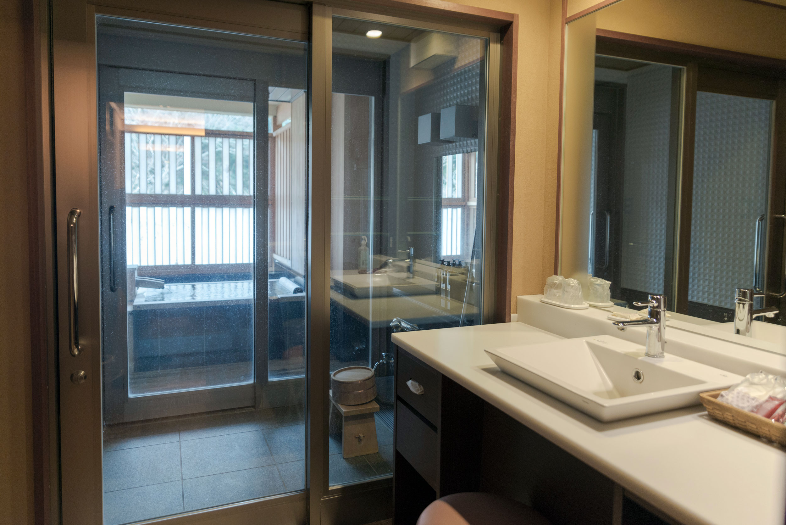 Bathroom with dual sinks, shower, and the private onsen tub outside