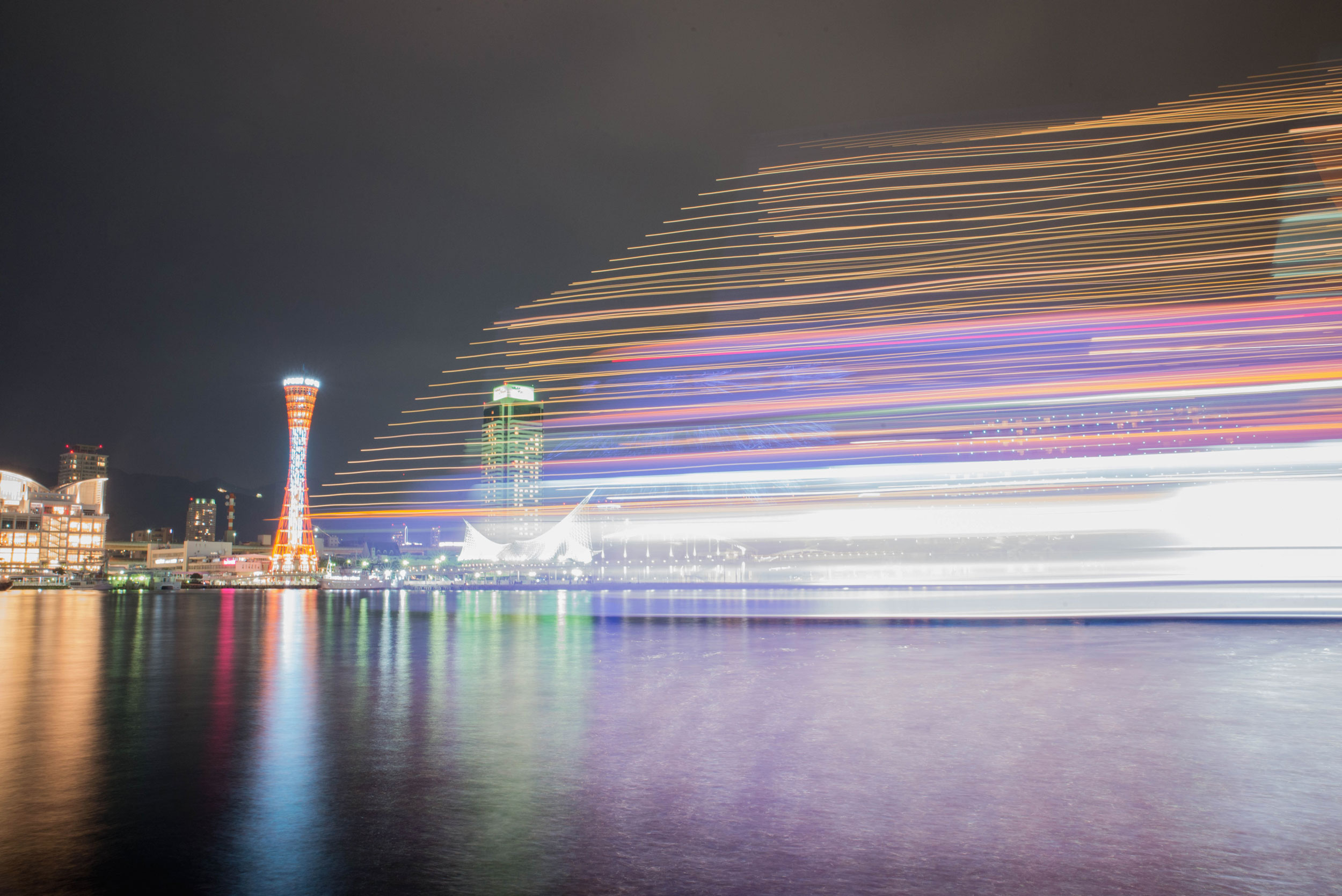 A passing boat creates light trails at the Port of Kobe