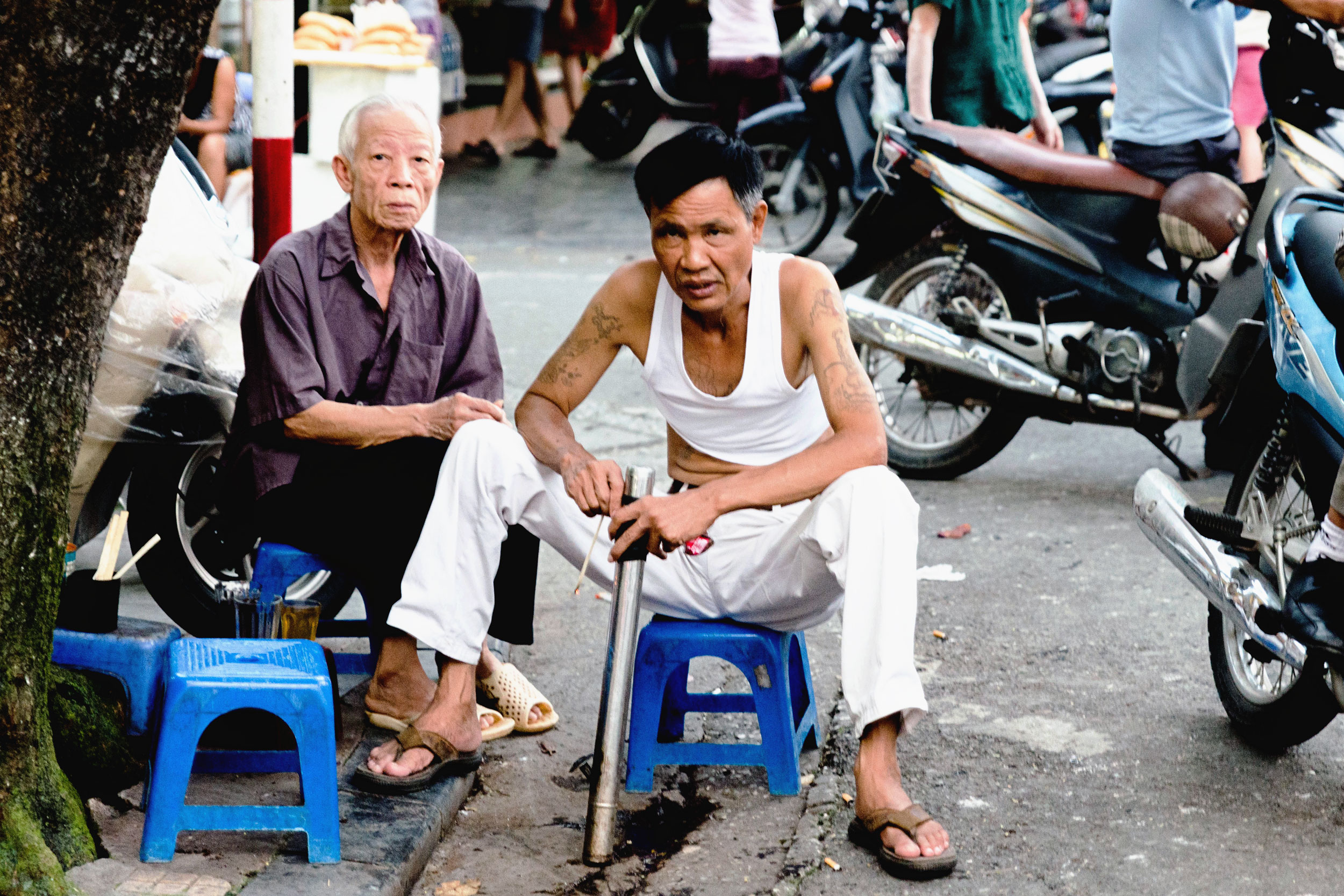 A man sitting on a curb in Hanoi