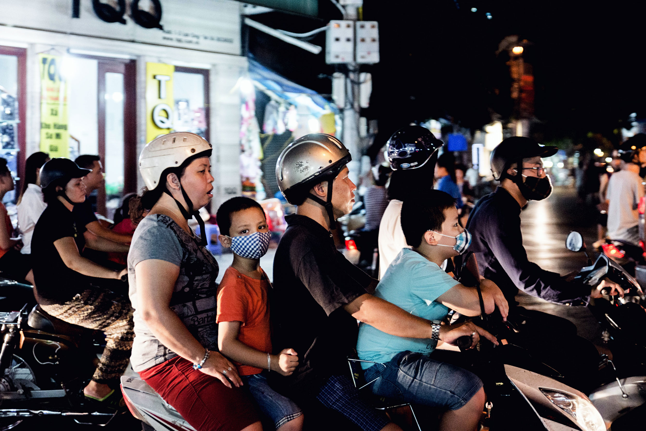A family rides together on a moped in Hanoi