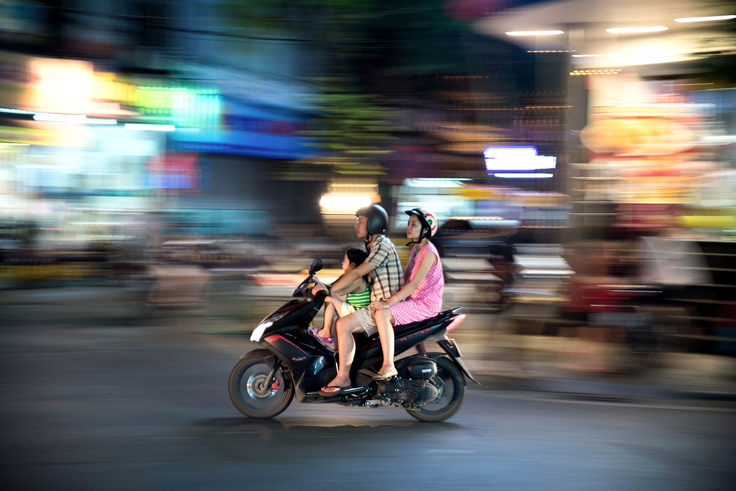 A family rides on a moped together in Hanoi