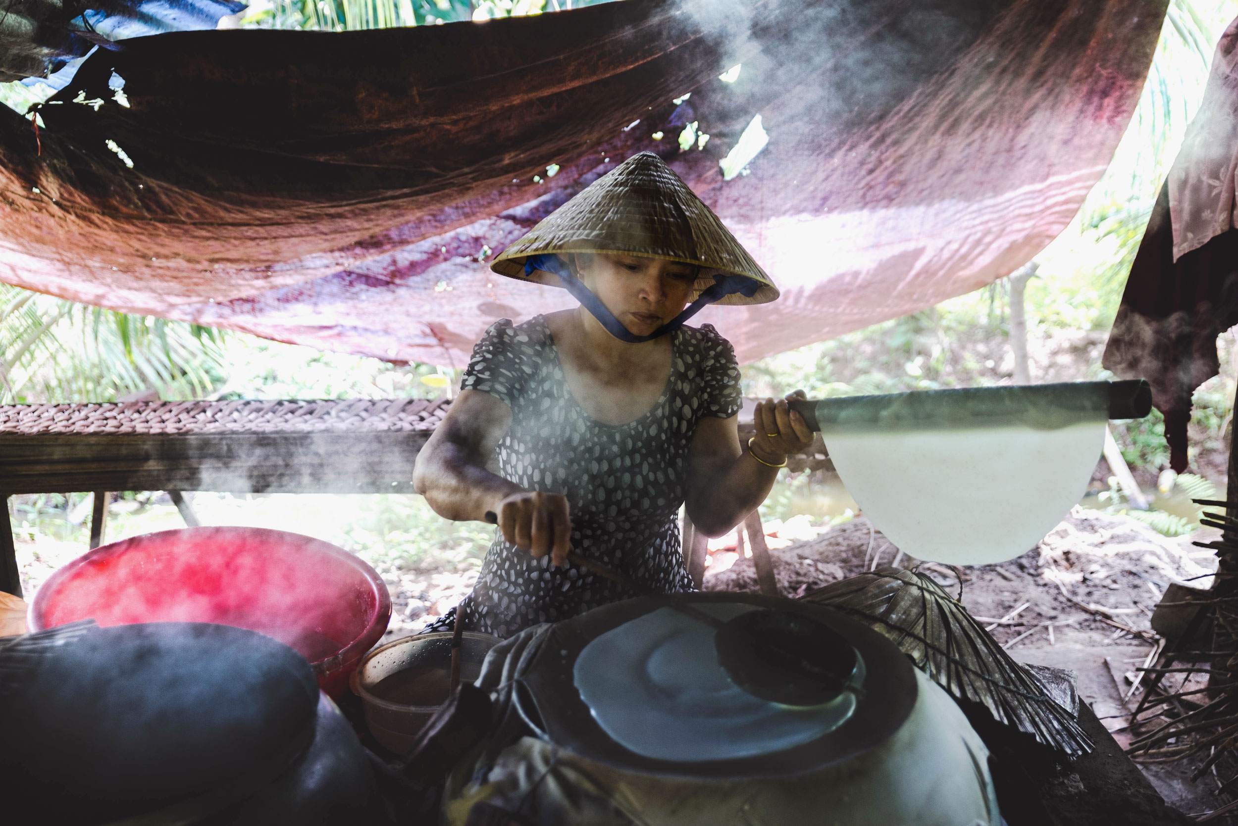 A woman making rice paper by hand.