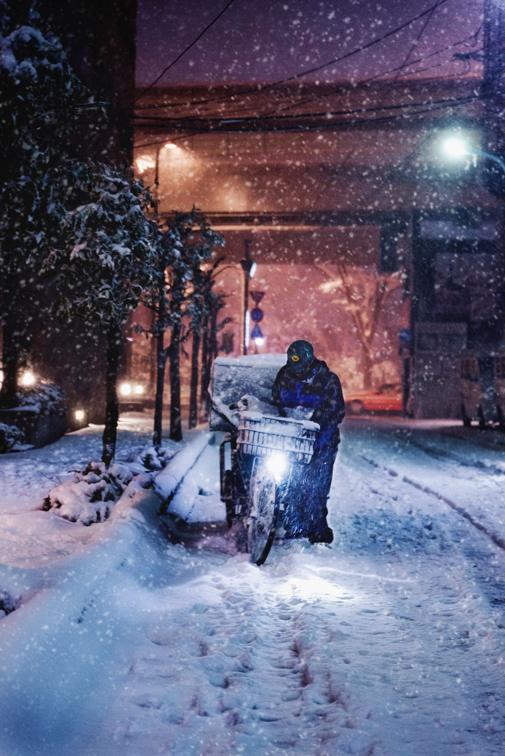 A Kuroneko Yamato delivery man delivering packages on a bicycle in the thick snow in Setagaya.