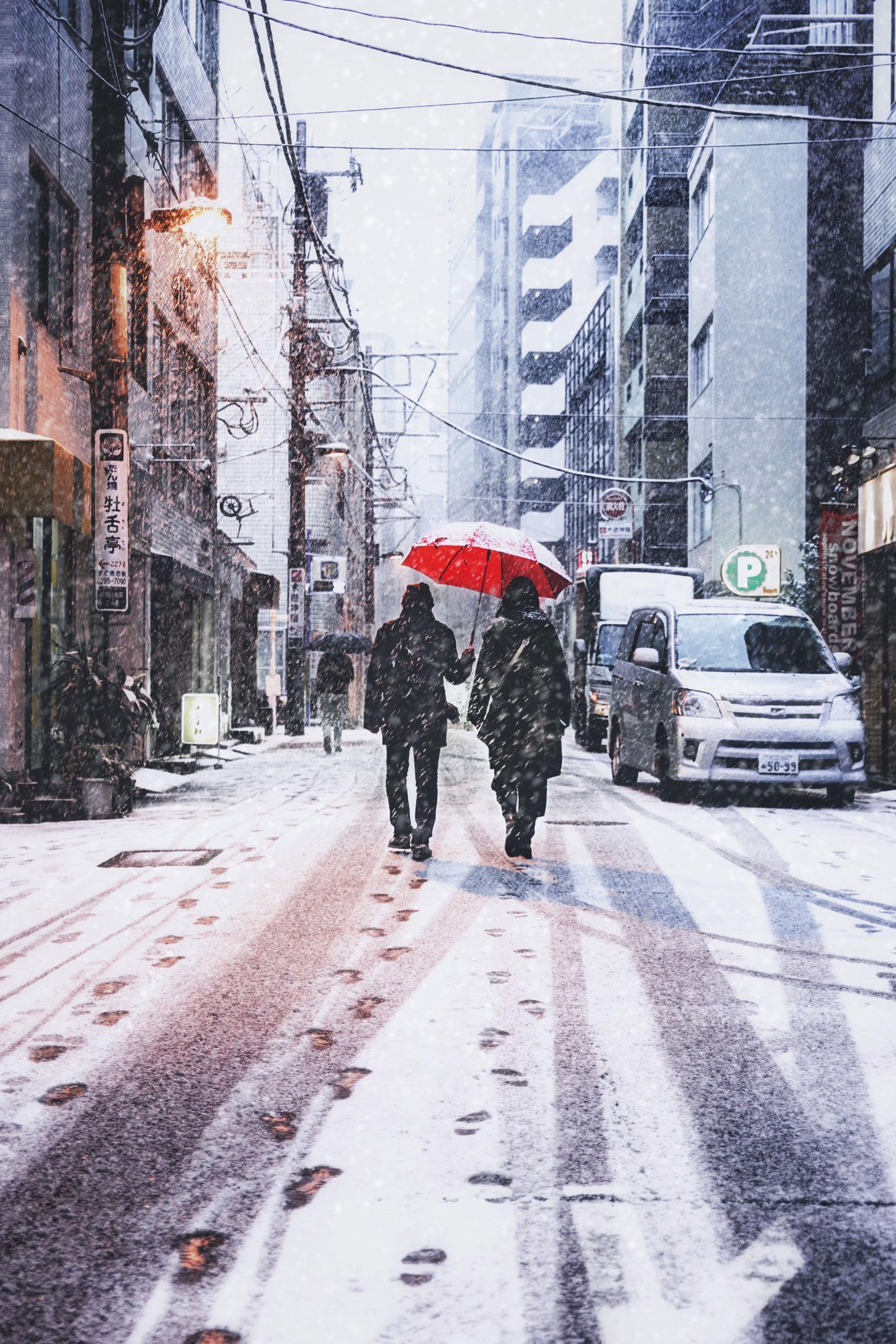 A couple shares an umbrella under the snow near Ochanomizu.