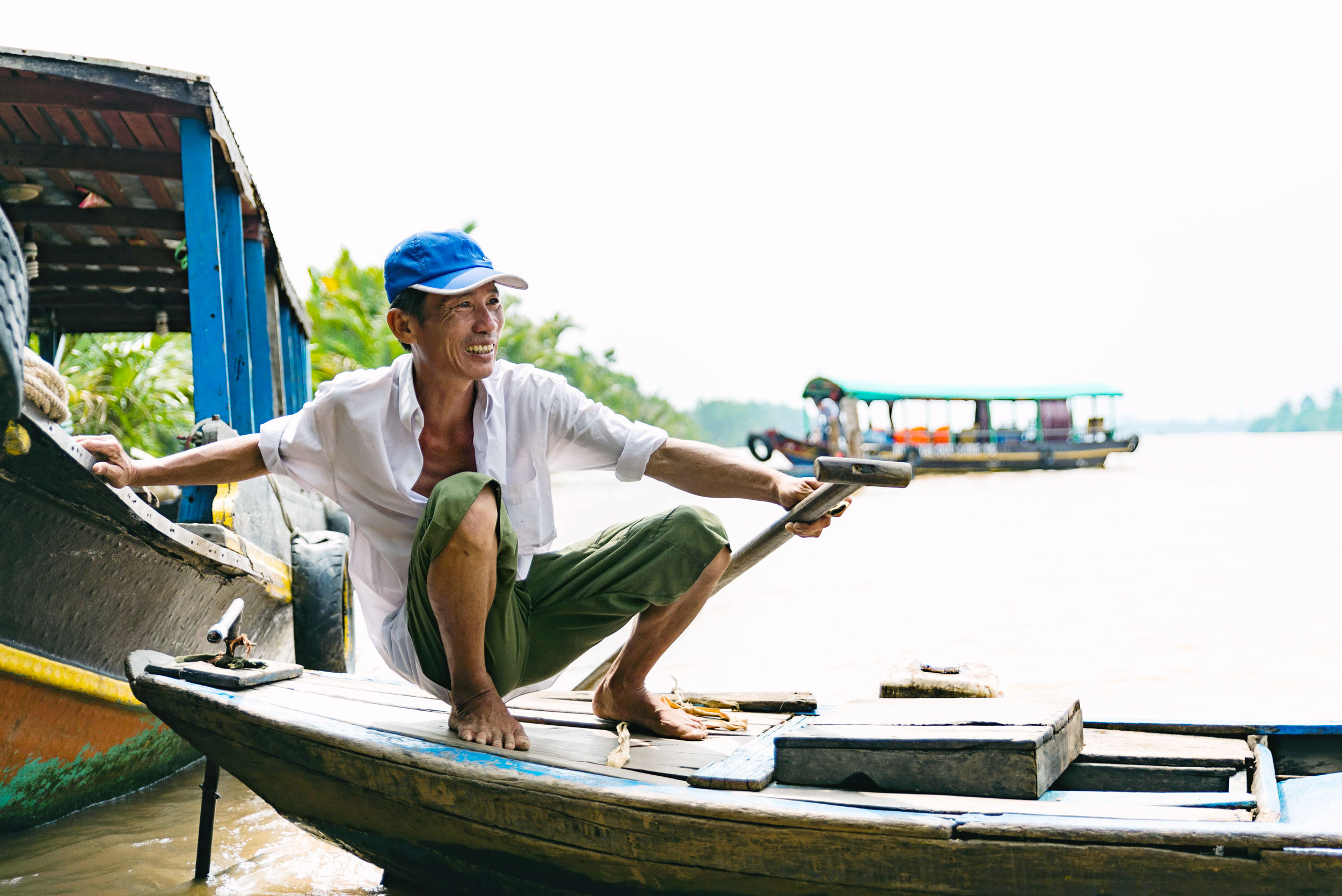 A man smiles while on his boat on the Mekong river