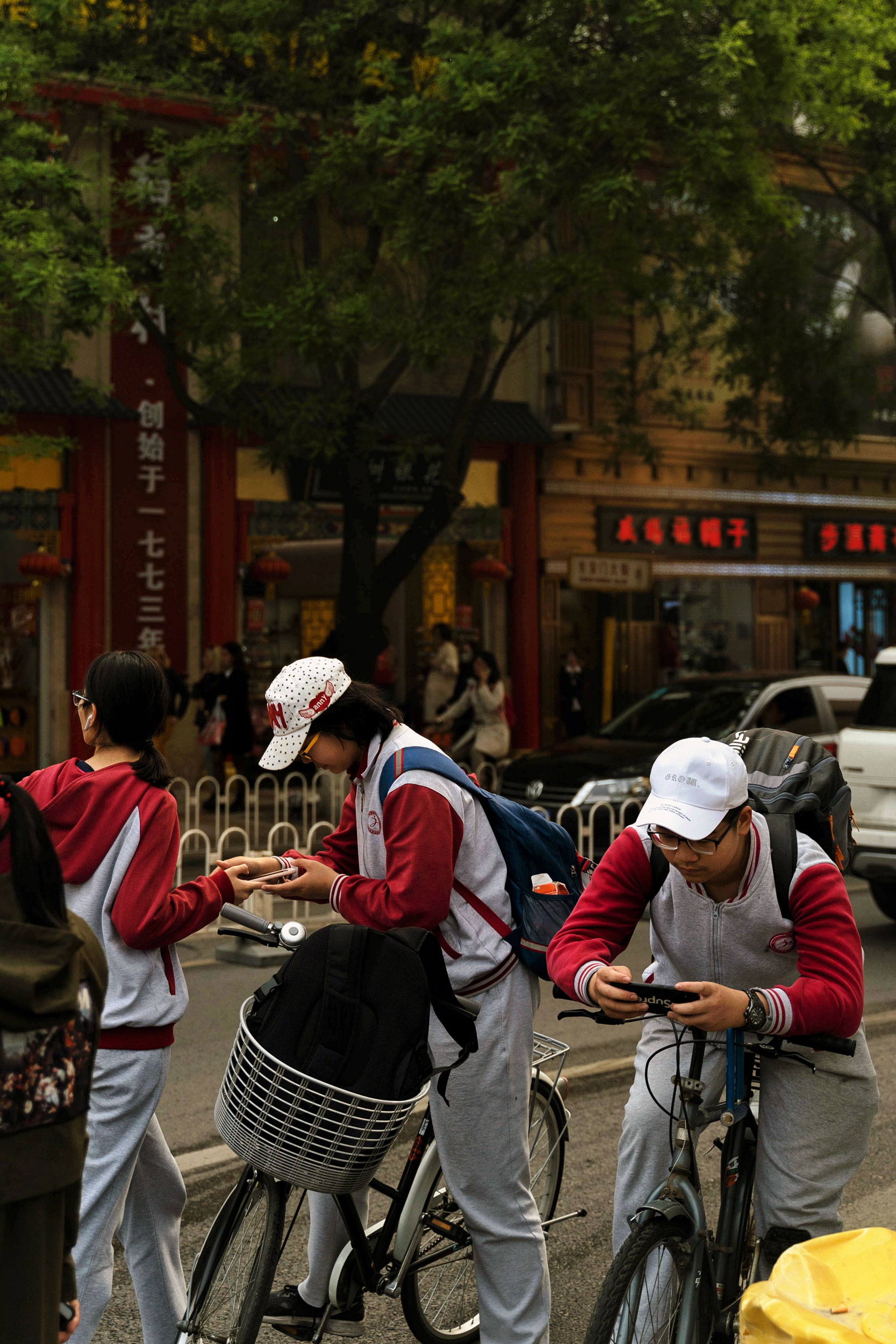 Some Chinese students take a break on their bicycles in Wangfujin.