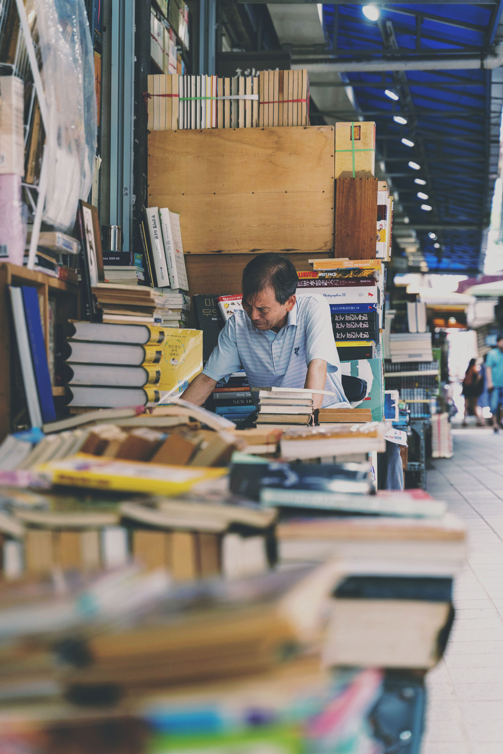 A bookstore owner immersed in books at Bosu Dong Book Street