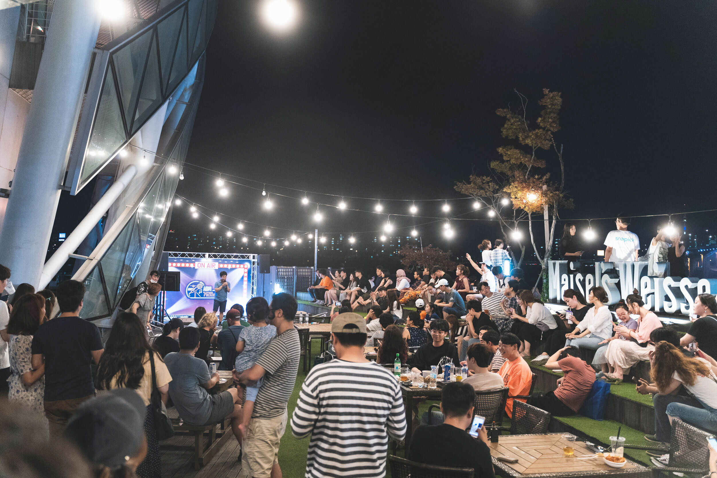 People eating and drinking, listening to opem mic karaoke at a Somesevit (Sebitseom) building
