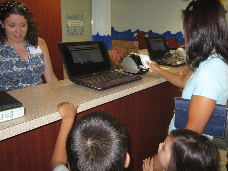 Mom checks in with ACS at the preschool check-in desk.