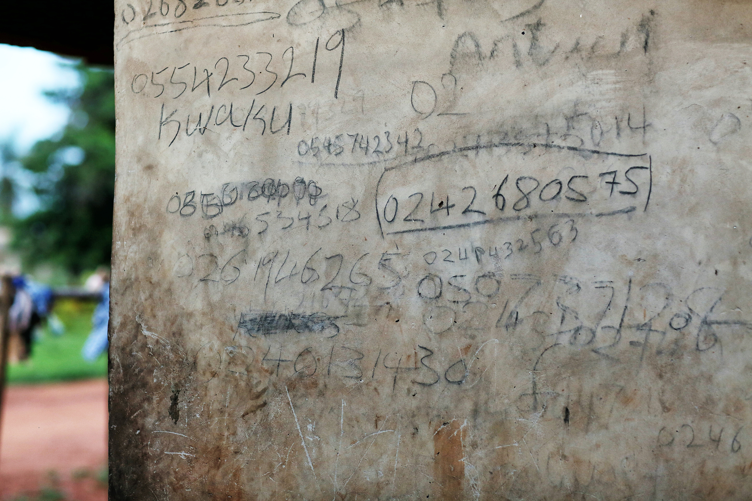 A series of phone numbers on a wall in Patience's family home.
