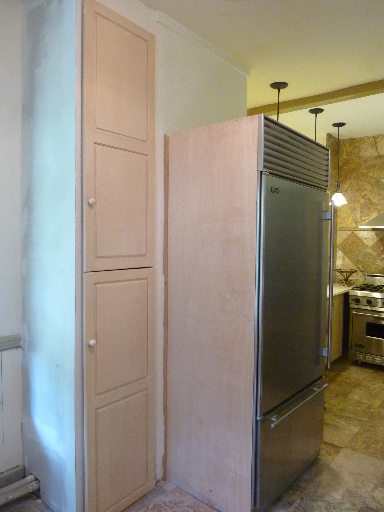 Cabinet doors were reconfigured to build a floor-to-ceiling cabinet.