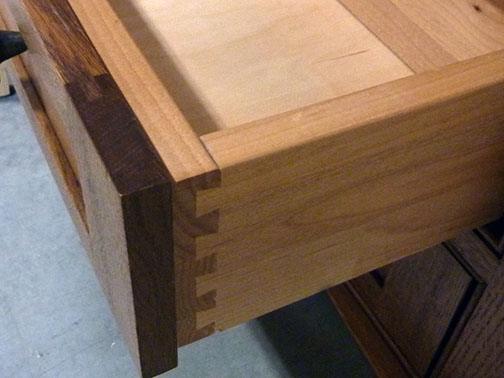 Here, the darker hardwood front panel is attached to the front of the drawer box, and a dovetail joint is visible. Slides are underneath.