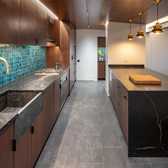 Walnut cabinets by Imperia topped with soapstone counters and soapstone farmer sink