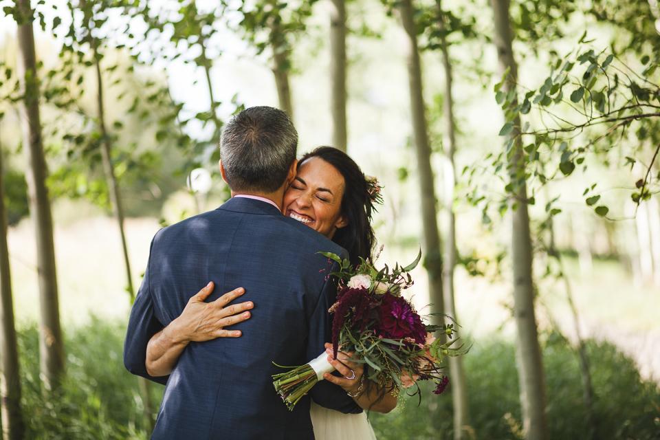 aspen colorado wedding bride smiling hugging groom