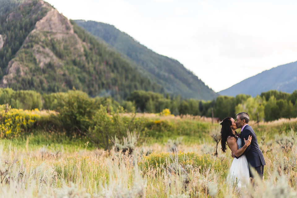 bride groom kissing in front of mountains in aspen colorado wedding