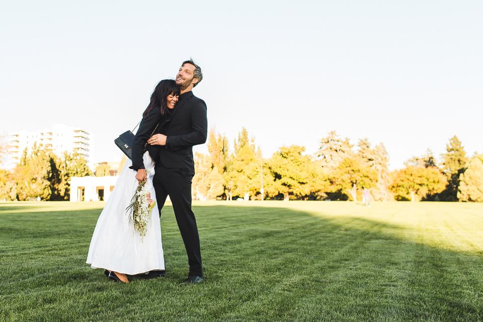 bride and groom laughing in congress park at wedding denver colorado
