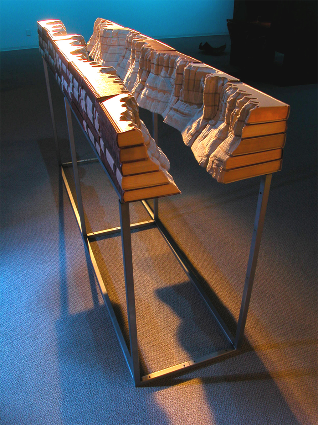 Guy Laramée,  The Grand Library , 2004,altered book, pigment, metal stand, 8 feet x 21 x 44 inches, artwork and image courtesy of the artist and JHB Gallery, New York