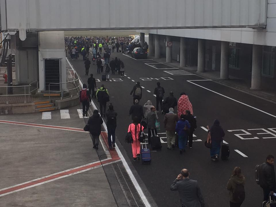 Crowds evacuating towards the tarmac.