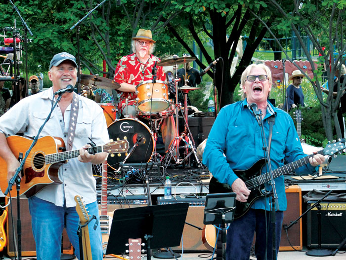 """Kevin Odegard, right, sings and mans an electric guitar as Jeff Dayton, left, plays the acoustic guitar and Scott Sansby plays the drums during the annual """"Salute to the Music of Bob Dylan"""" Aug. 1 at Veterans' Memorial Amphitheater in St. Louis Park. (Sun Sailor staff photo by Seth Rowe)"""