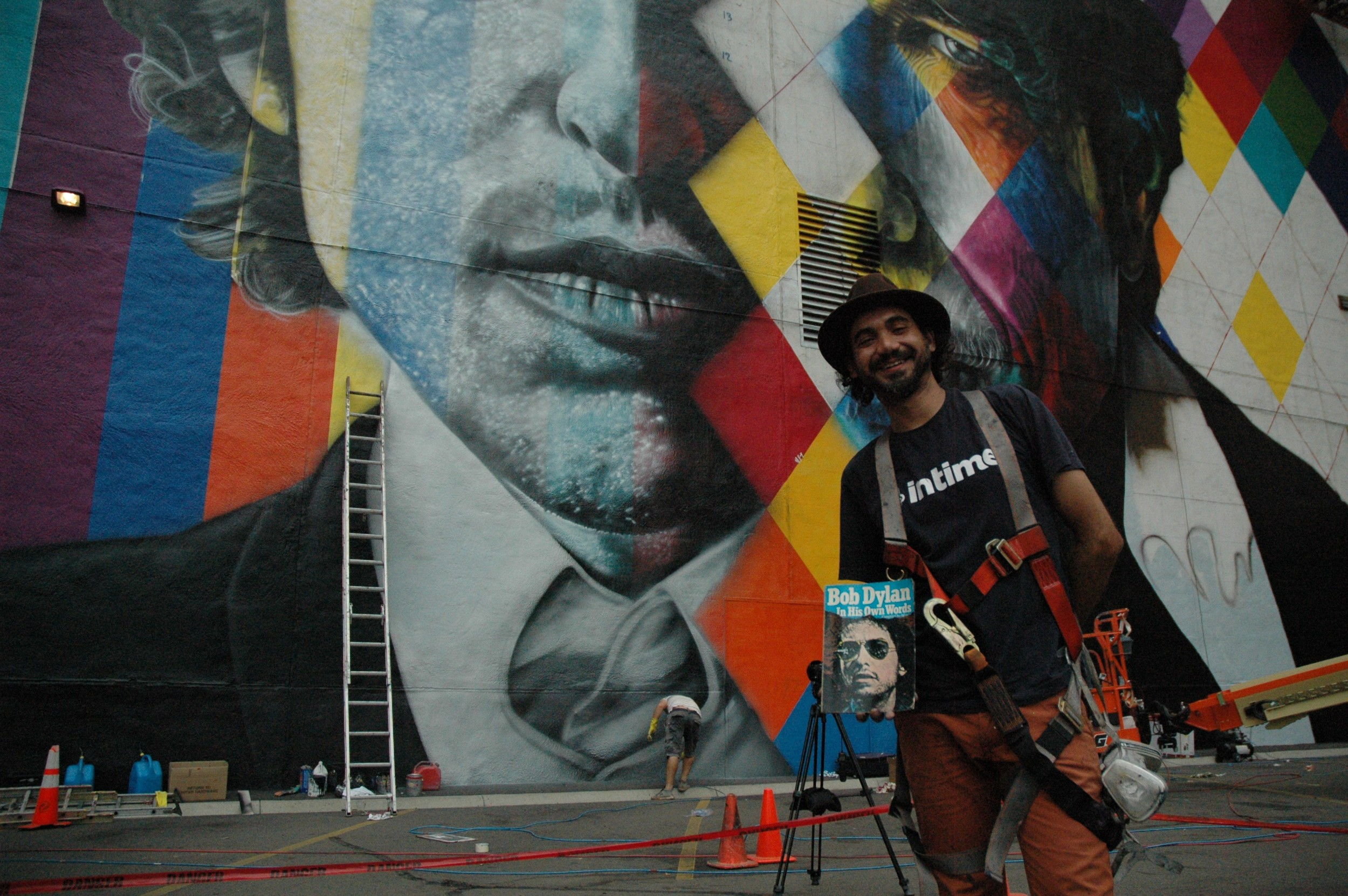 Eduardo Kobra and a copy of Dylan's autobiography, which serendipitously was found in the building that he's painting.