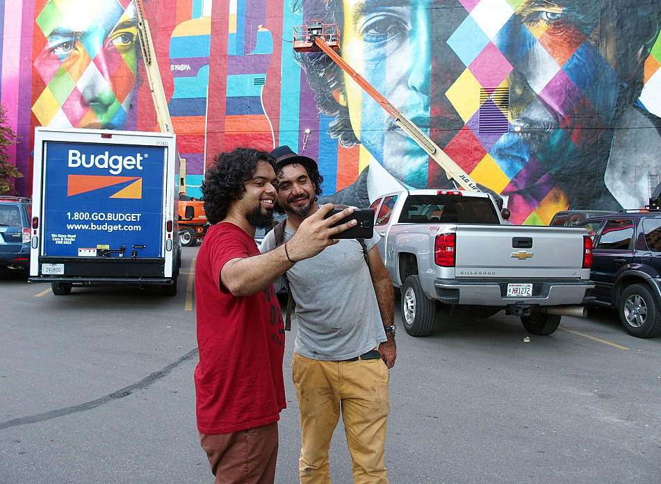 Despite a language barrier with most passersby, Eduardo Kobra was happy to pose with visitors for photographs when he took a break from painting, Sept. 5, 2015.