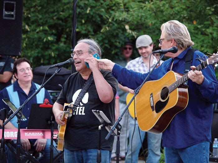 Kevin Odegard, right, pretends to pull a cell phone away from Billy Hallquist in the midst of a Salute to the Music of Bob Dylan concert in St. Louis Park. (Submitted photo)