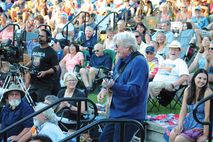 Kevin Odegard, who helped organize the Summer of Love concert July 29 in Wolfe Park, jams out in the crowd during a medley of classic tunes popular during the 1960s. (Sun Sailor staff photo by Seth Rowe)