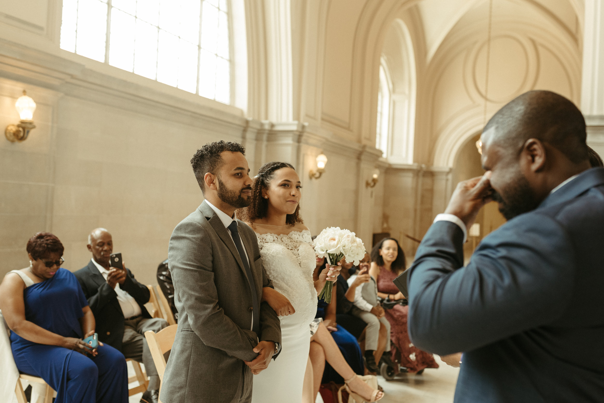 groom cries at san francisco city hall wedding ceremony. photo by amira maxwell