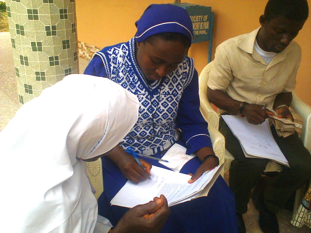 A young muslim woman receives her loan. While Anawim is a Catholic organization, they do not discriminate with regard to whom they offer assistance.