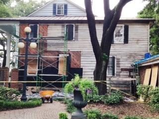 All of the brick is now off of the Front Street facade of the Kaminski House. The diagonal wooden boards cover an area that was once open porches. Black tar paper is being installed in these areas to protect the house from the elements.