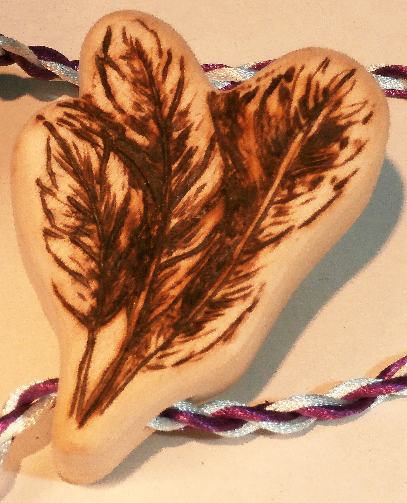 Wood burnt detail of feathers on teether handle for baby shower gift.