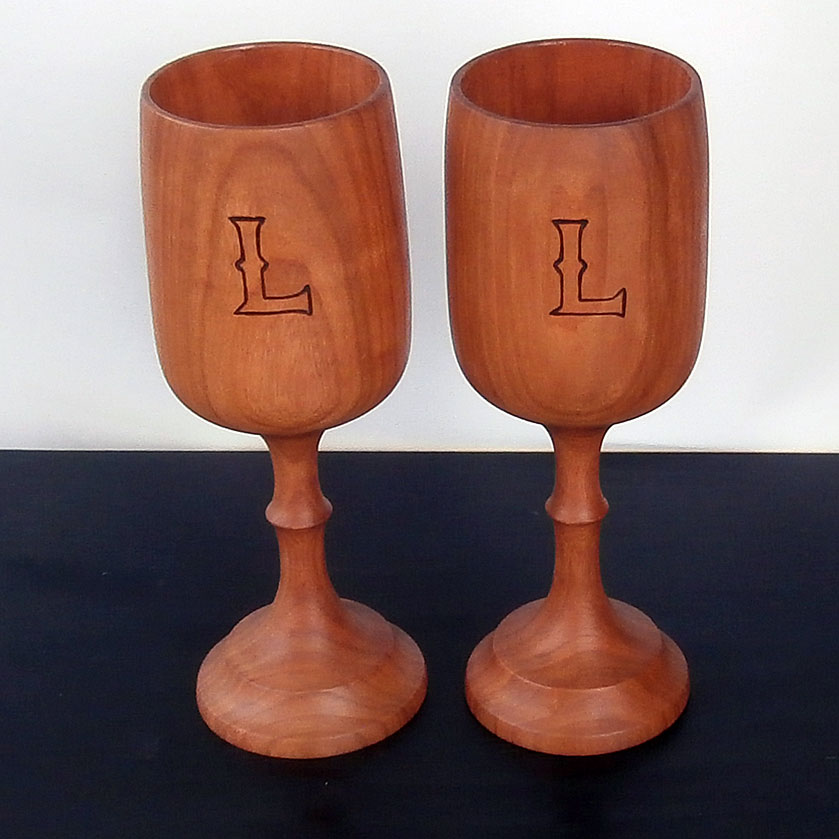 """Anniversary present of a matching set of wine goblets with a wood burnt letter """"L"""". Made out of Cherry wood with a food safe epoxy coating on the inside."""