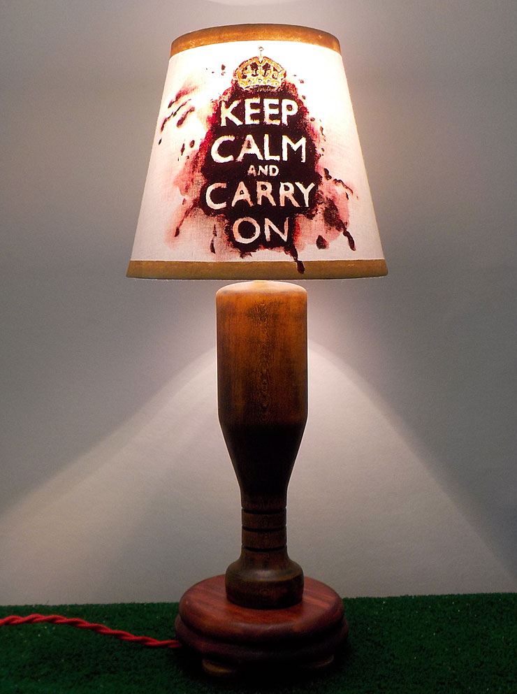 """Hand painted shade with the """"Keep Calm and Carry On"""" motivational saying, first printed on posters by the British government in preparation for the Second World War, on a red/blood splattered background. The base is made of Poplar wood turned on the lathe to look like a baseball bat and stained with amber brown and cinnamon red to make an antique finish."""
