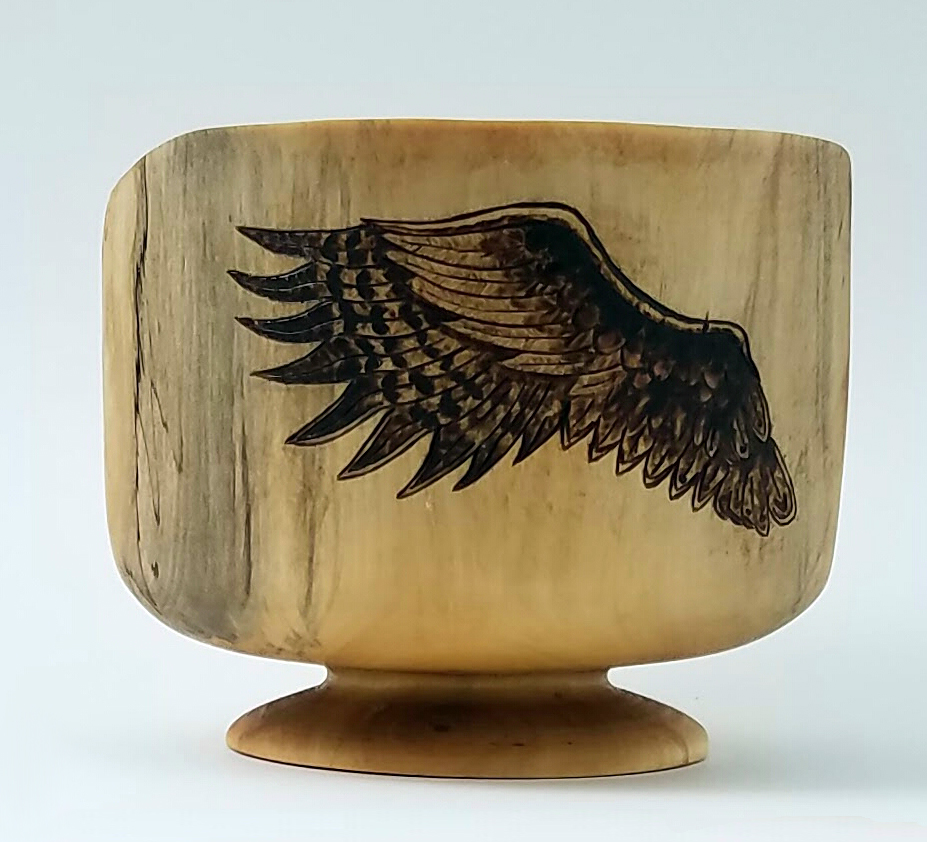 On the side of the bowl, Sarah wood burnt wings.