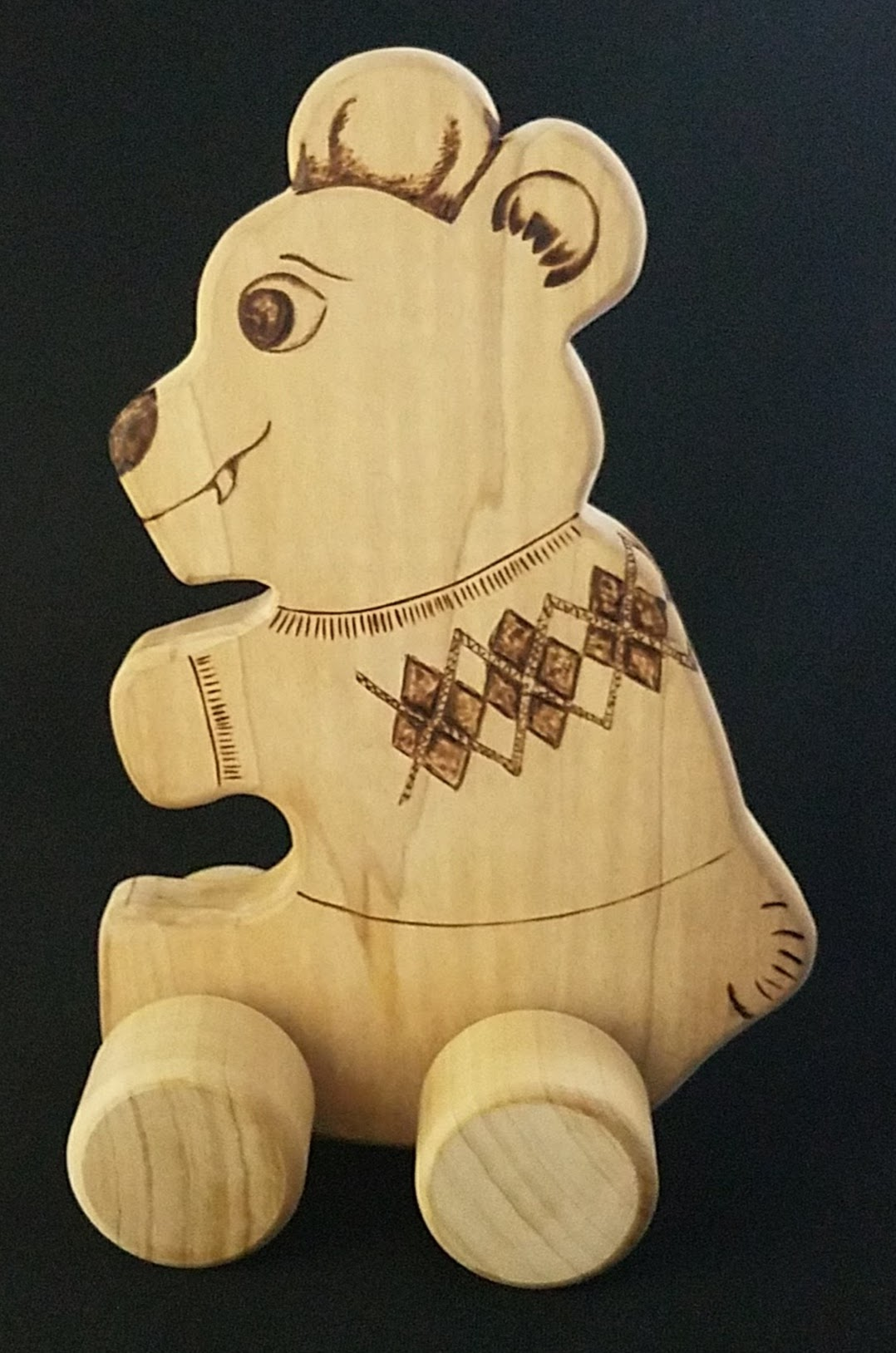 Too cute natural Poplar wood with wood burnt details, rolling teddy bear in argyle sweater.