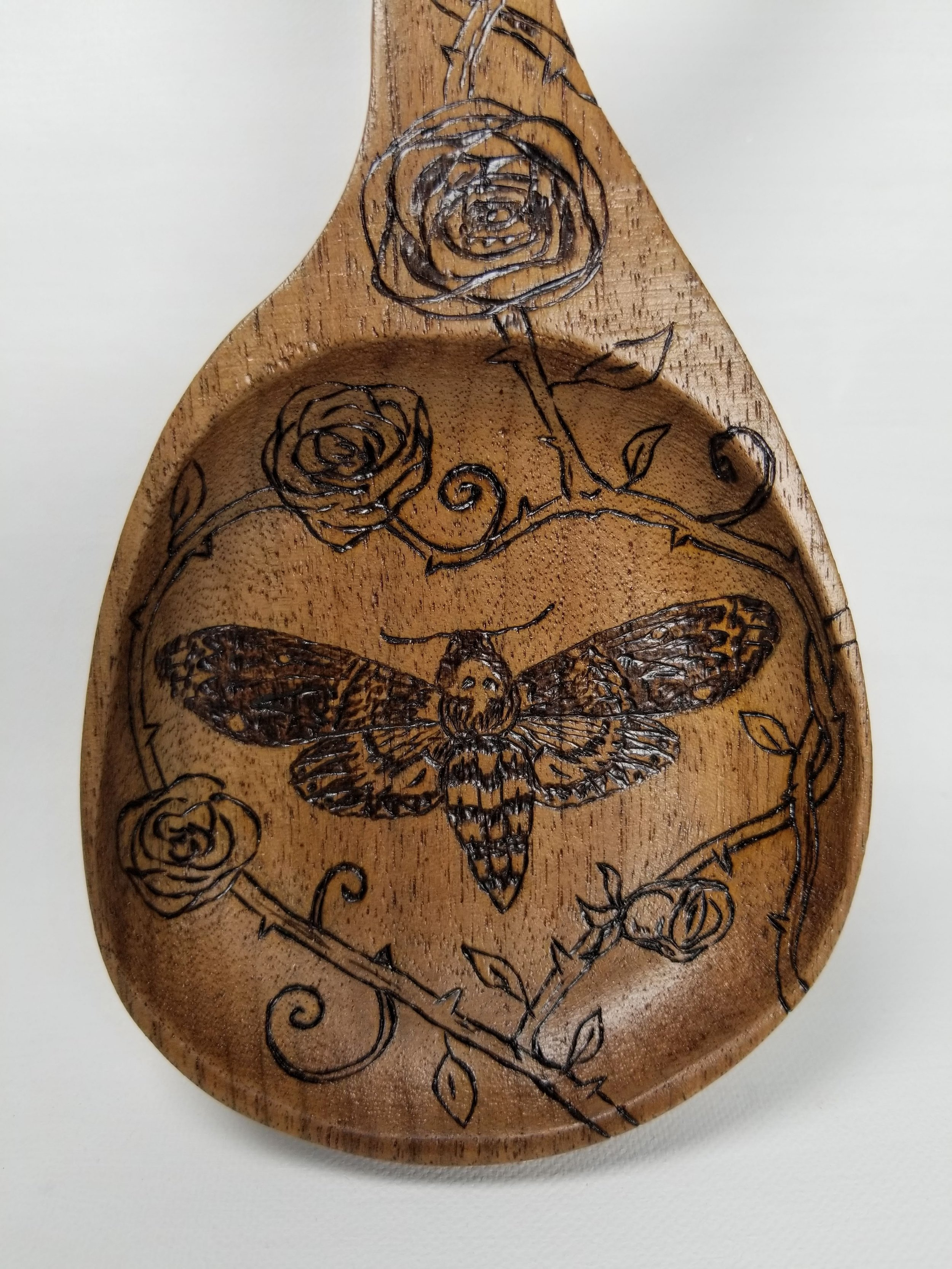 Death's-head hawkmoth pyrographic drawing in a heart of rose vines.