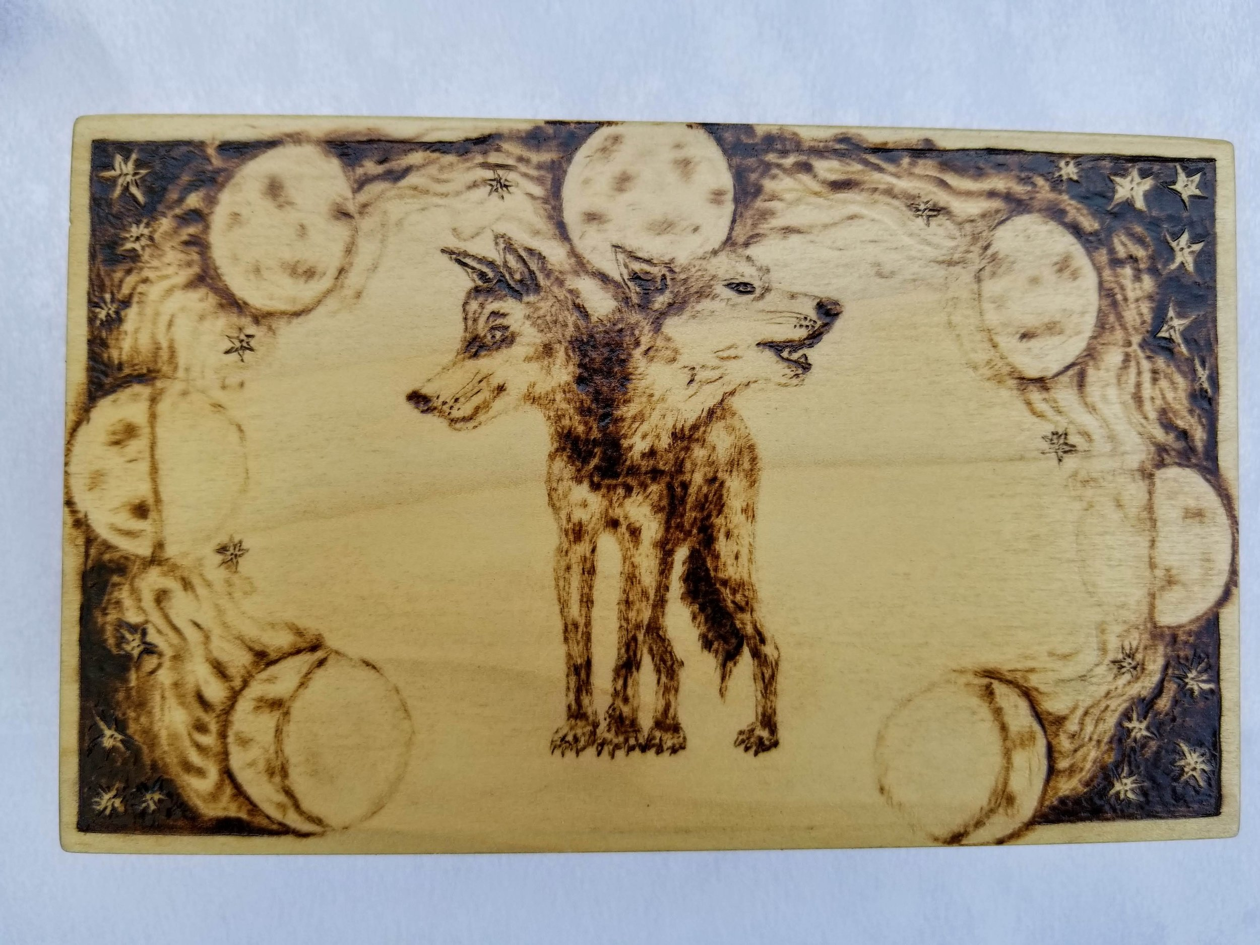 The lid of the box has a two headed wolf with phases of the moon.